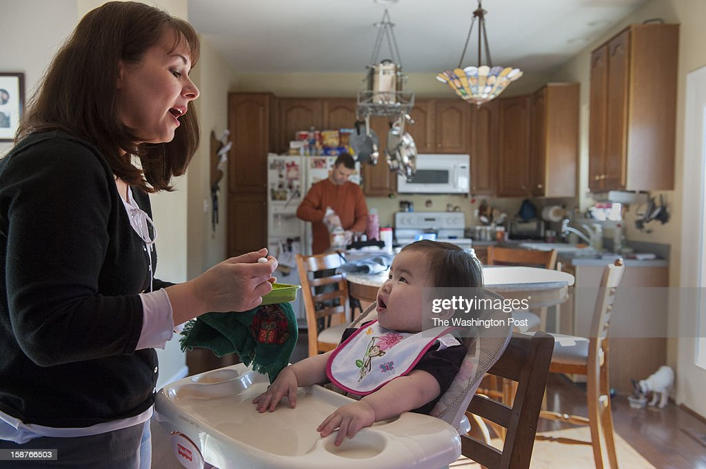 Lunchtime at the Raineses involves Carol feeding 17-month-old Hannah lunch as her husband, Adam prepares lunch after feeding Penny, their dog, Sunday, December 23, 2012 in Westminster, MD. The couple picked up their adopted daughter from Korea two weeks ago.