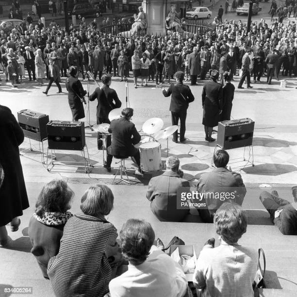 Lunchtime rhythm for the crowds standing in the sunshine outside St Paul's Cathedral London They are listening to a performance given in front of the...