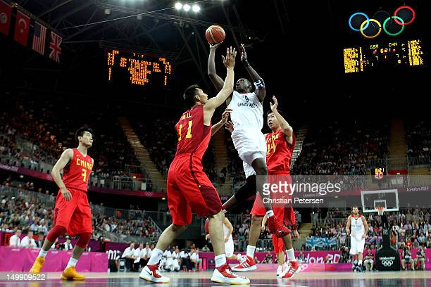 Luol Deng of Great Britain drives for a shot attempt against Yi Jianlian and Wang Zhizhi of China during the Men's Basketball Preliminary Round match...