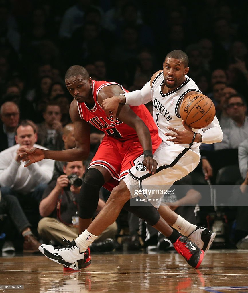 Luol Deng of the Chicago Bulls and CJ Watson of the Brooklyn Nets battle for a loose ball during Game Five of the Eastern Conference Quarterfinals of...