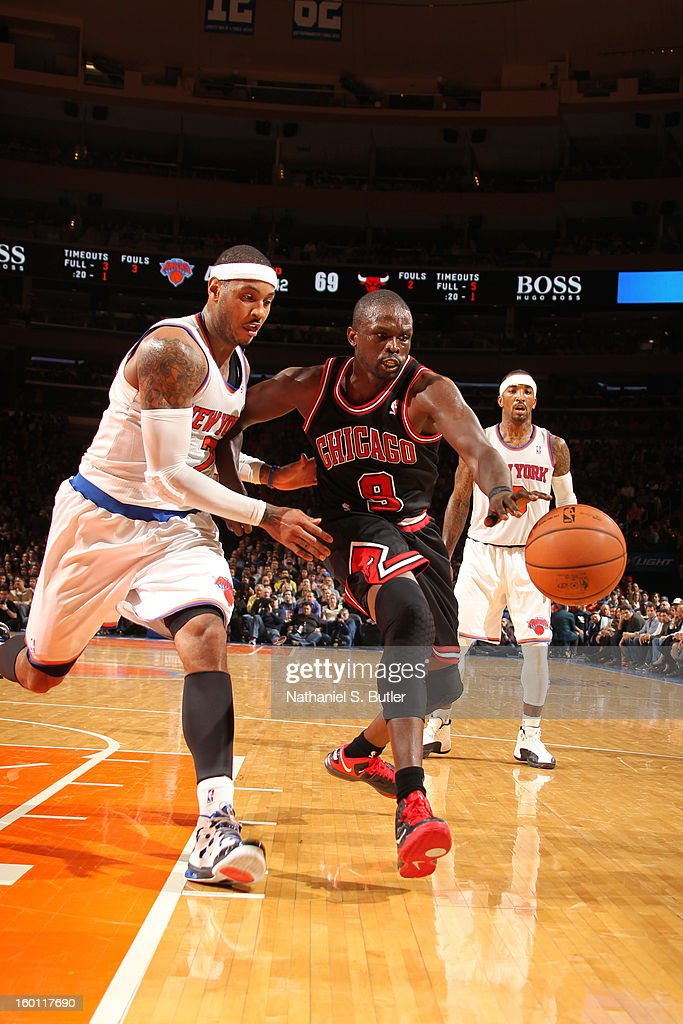 Luol Deng #9 of the Chicago Bulls battles for a loose ball against Carmelo Anthony #7 of the New York Knicks on January 11, 2013 at Madison Square Garden in New York City.