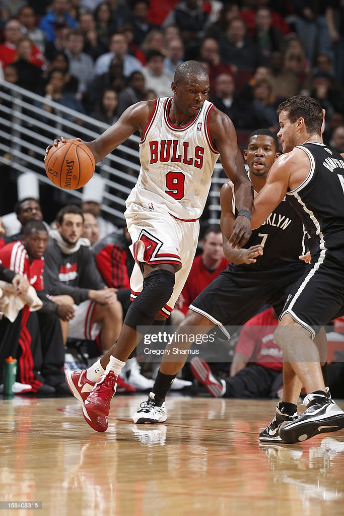 Luol Deng #9 of the Chicago Bulls drives against Joe Johnson #7 and Kris Humphries #43 of the Brooklyn Nets on December 15, 2012 at the United Center in Chicago, Illinois.