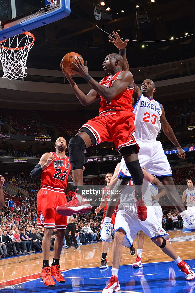 Luol Deng #9 of the Chicago Bulls drives to the basket against Jason Richardson #23 of the Philadelphia 76ers on December 12, 2012 at the Wells Fargo Center in Philadelphia, Pennsylvania.