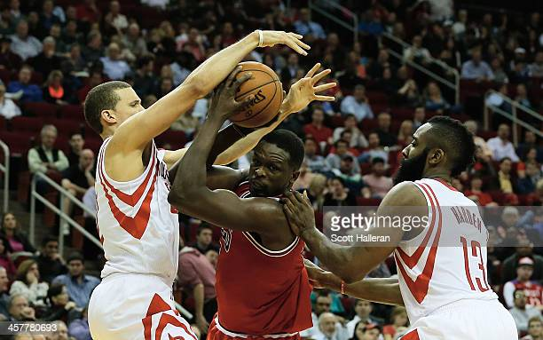 Luol Deng of the Chicago Bulls drives with the ball against Francisco Garcia and James Harden of the Houston Rockets during the game at Toyota Center...