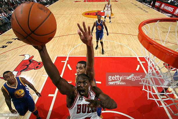 Luol Deng of the Chicago Bulls goes to the basket past Brandan Wright AND Monta Ellis of the Golden State Warriors during the NBA game on November 11...