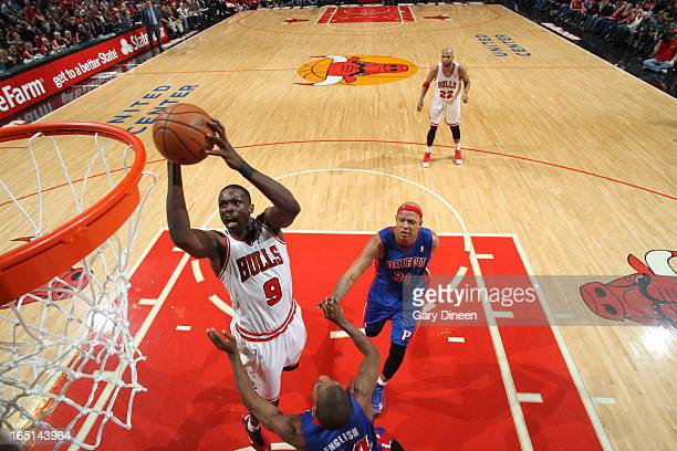 Luol Deng of the Chicago Bulls goes to the basket past Kim English and Charlie Villanueva of the Detroit Pistons on March 31 2013 at the United...