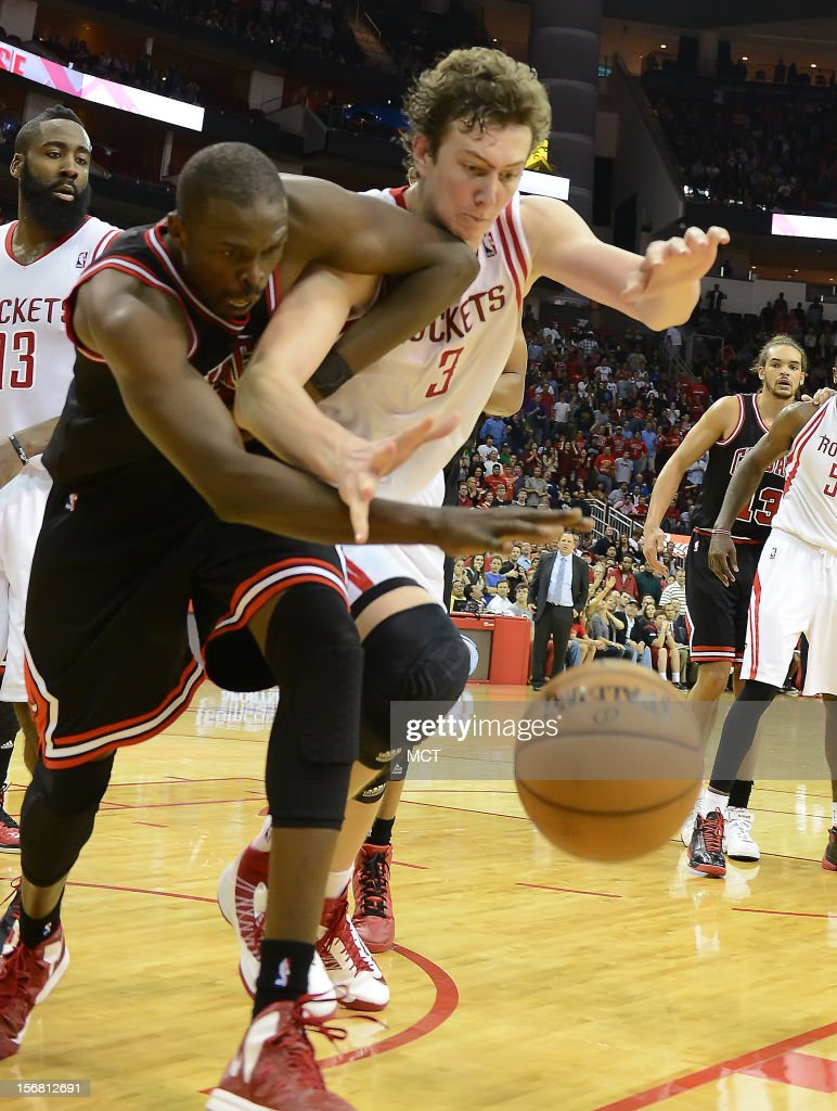 Luol Deng (9) of the Chicago Bulls, left, and Omer Asik (3) of the Houston Rockets battle for a loose ball in the second half of the Rockets' 93-89 victory on Wednesday, November 21, 2012, in Houston, Texas.