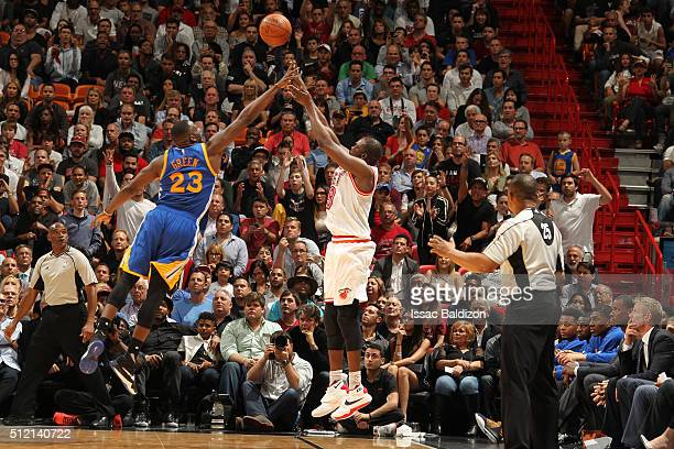 Luol Deng of the Miami Heat shoots the ball against Draymond Green of the Golden State Warriors on February 24 2016 at American Airlines Arena in...