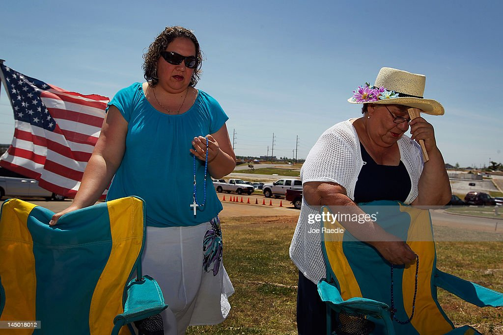 Lupita Reyes (L) and Rodriguez Hortenci pray during a service in front of an iron cross that is all that remains of St. Mary's church after it was destroyed by the tornado one year ago today on May 22, 2012 in Joplin, Missouri. The EF-5 tornado devastated the leaving behind a path of destruction along with 161 deaths and hundreds of injuries, but one year later there are signs that the town is beginning to recover.