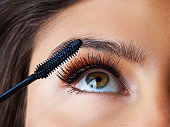 Shot of a gorgeous young woman applying mascara against a dark background