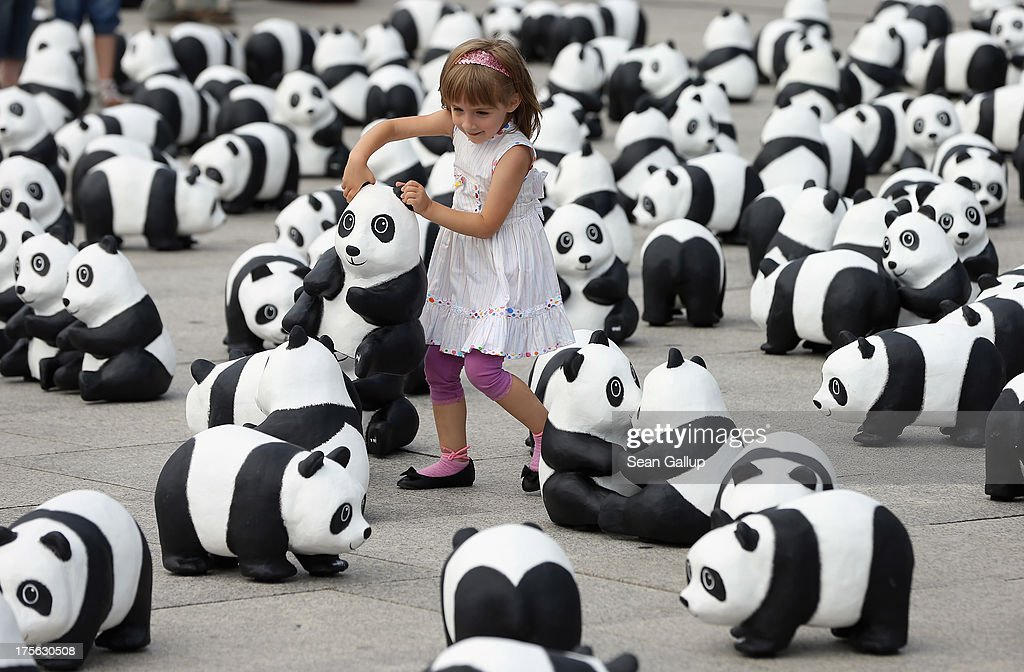 Lusitta, 4, carries a styrofoam panda bear sculpture among 1,599 more displayed in front of Hauptbahnhof main railway station by the World Wildlife Fund on August 5, 2013 in Berlin, Germany. The WWF is celebrating its 50th anniversary and is drawing attention to the fact that only 1,600 panda bears remain in the wild. The display will soon travel to 25 other cities in Germny.