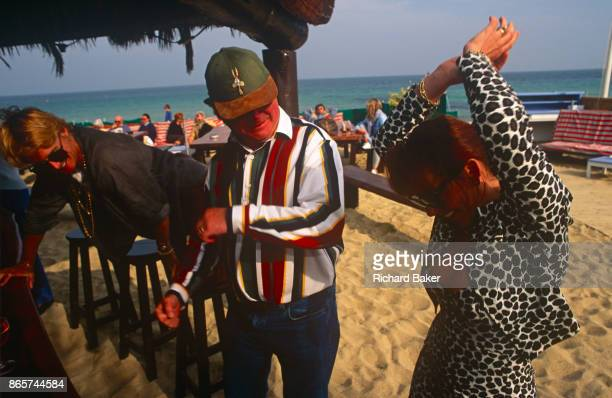 Lusty letching middleaged men watch the body of a lady as she boogies on a Cote d'Azur beach on 14th April 1996 in St Tropez France