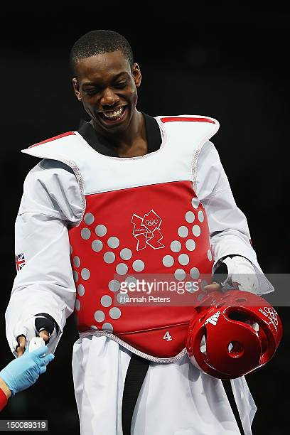 Lutalo Muhammad of Great Britain forgets his mouthguard before competing against Farkhod Negmatov of Tajikistan during the Men's 80kg Taekwondo...