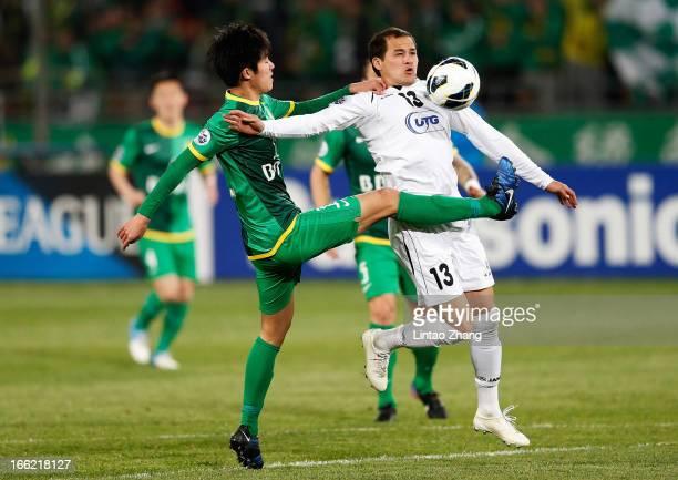 Lutfulla Turaev of Bunyodkor challenges Li Tixiang of Beijing Guoan during the AFC Champions League Group match between Bunyodkor and Beijing Guoan...