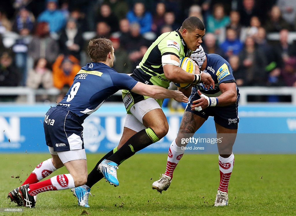 <a gi-track='captionPersonalityLinkClicked' href=/galleries/search?phrase=Luther+Burrell&family=editorial&specificpeople=871965 ng-click='$event.stopPropagation()'>Luther Burrell</a> of Northampton Saints is tackled by <a gi-track='captionPersonalityLinkClicked' href=/galleries/search?phrase=Dwayne+Peel&family=editorial&specificpeople=206685 ng-click='$event.stopPropagation()'>Dwayne Peel</a> (L) and <a gi-track='captionPersonalityLinkClicked' href=/galleries/search?phrase=Sam+Tuitupou&family=editorial&specificpeople=540375 ng-click='$event.stopPropagation()'>Sam Tuitupou</a> of Sale Sharks during the Aviva Premiership match between Sale Sharks and Northampton Saints at A J Bell Stadium on March 22, 2014 in Salford, England