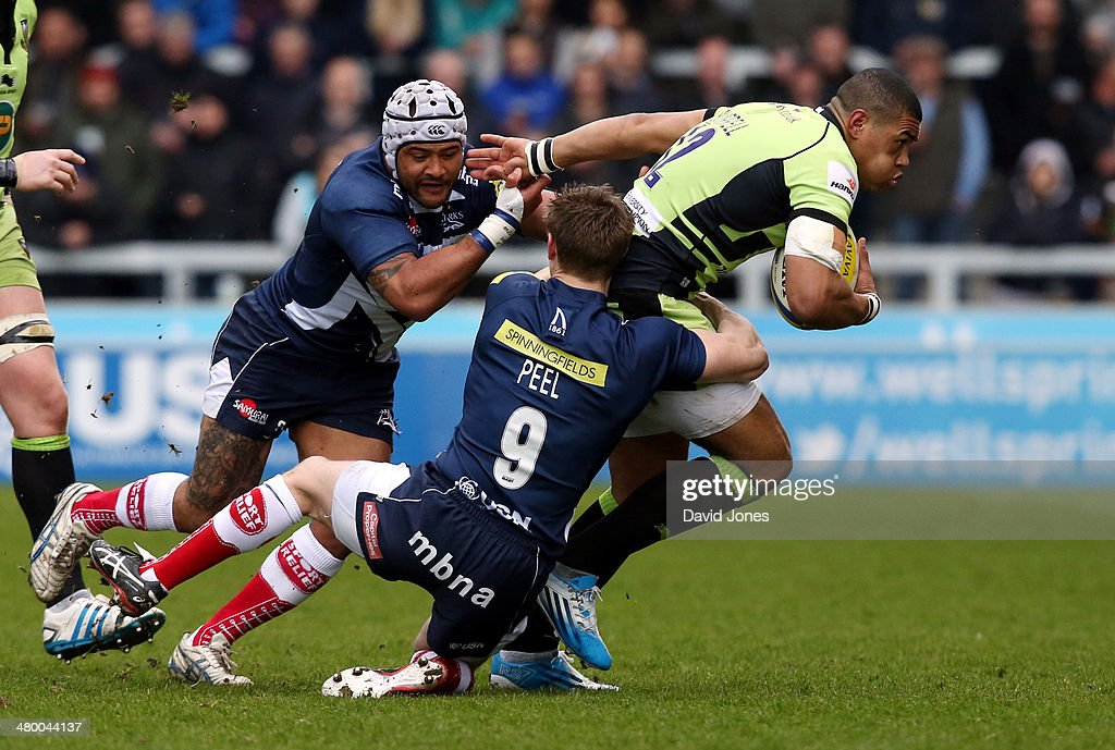 Luther Burrell of Northampton Saints is tackled by Dwayne Peel of Sale Sharks during the Aviva Premiership match between Sale Sharks and Northampton Saints at A J Bell Stadium on March 22, 2014 in Salford, England