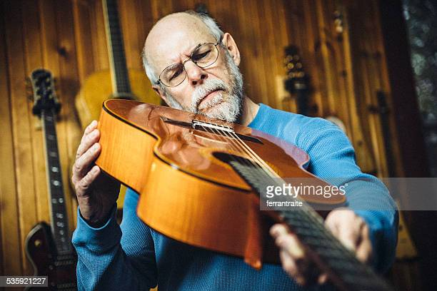 Luthier examining a classic guitar in workshop