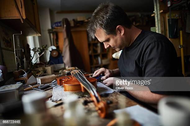 Luthier in workshop working on violin