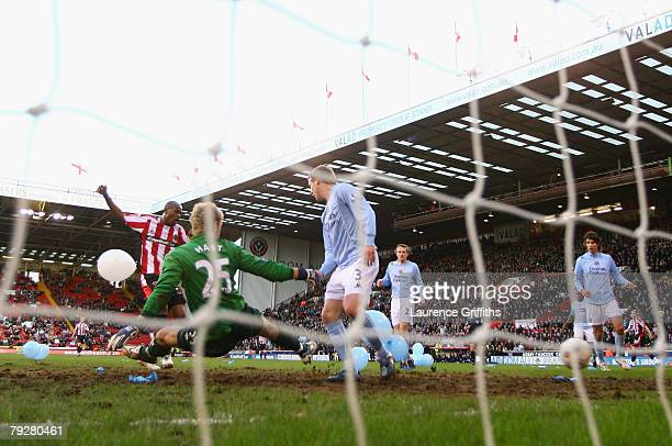 Luton Shelton of Sheffield United scores the opening goal past Joe Hart of Manchester City during the EON sponsored FA Cup Fourth Round match between...