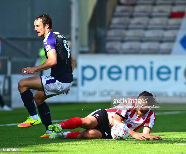 Luton Town's Danny Hylton is tackled by Lincoln City's Michael Bostwick during the Sky Bet League Two match between Lincoln City and Luton Town at...