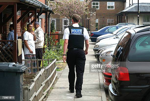 A British policeman walks along the pavement towards a group of residents and relatives outside an arrested man's home in Luton north of London 24...