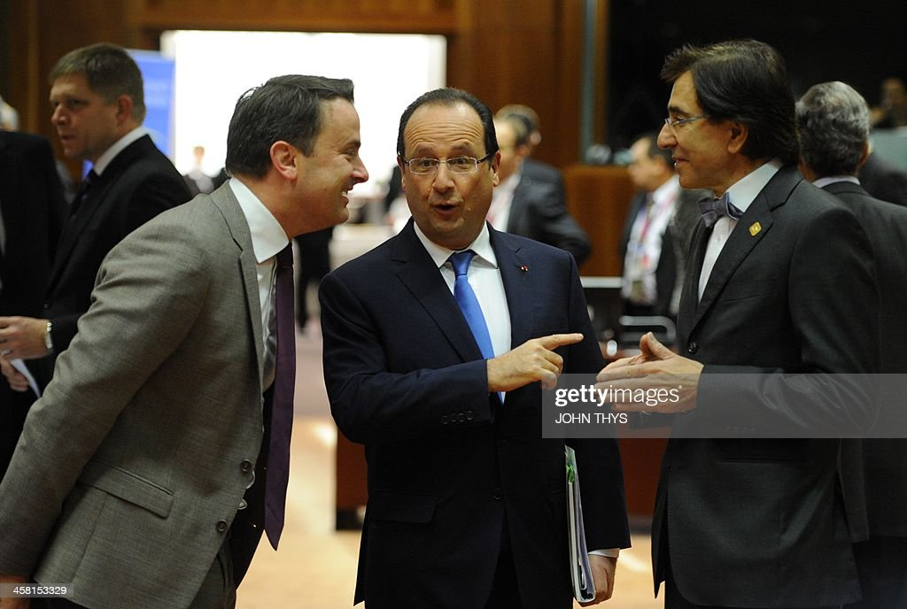 Luxembourg Prime Minister Xavier Bettel talks to French President Francois Hollande and Belgian Prime Minister Elio Di Rupo during an EU summit...
