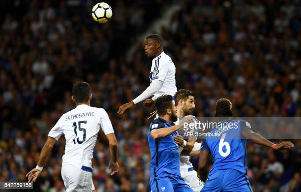 Luxembourg's defender Christopher Martins Pereira heads the ball next to France's forward Olivier Giroud during the FIFA World Cup 2018 qualifying...