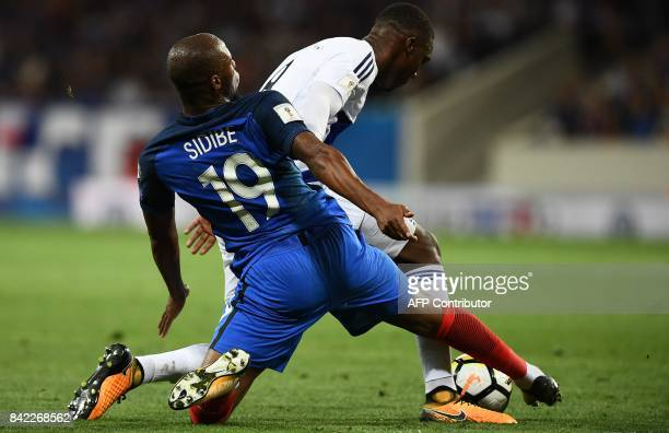 Luxembourg's defender Christopher Martins Pereira is tackled by France's defender Djibril Sidibe during the FIFA World Cup 2018 qualifying football...
