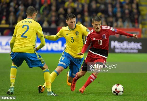 Luxembourg's midfielder Vincent Thill vies for the ball with Sweden's defender Mikael Lustig and Sweden's Victor Sweden's defender Victor Lindelof...