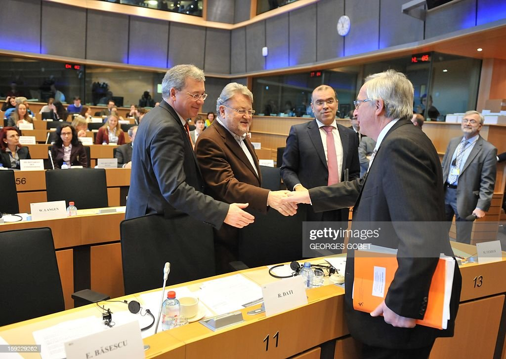 Luxembourg's Prime Minister and Eurogroup president Jean-Claude Juncker (R) shakes hands as he arrives at the commission meeting on 'Economic and Monetary Affairs' of the European Parliament on January 10, 2013, at the EU headquarters in Brussels. Jean-Claude Juncker will present his analysis of the political, economic and financial conditions in the euro area and answer questions from members of the EP Commission.