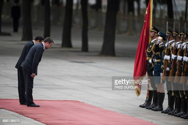 Luxembourg's Prime Minister Xavier Bettel and Chinese Premier Li Keqiang bow in front of an honour guard during a welcoming ceremony at the Great...