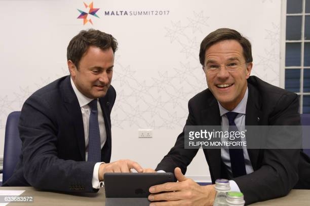 Luxembourg's Prime Minister Xavier Bettel and Netherland's Prime Minister Mark Rutte watch a tablet during an European Union summit on February 3...