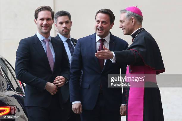 Luxembourg's Prime Minister Xavier Bettel and partner Gauthier Destenay are welcomed by the prefect of the papal household Georg Gaenswein as they...