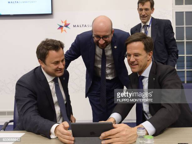 Luxembourg's Prime Minister Xavier Bettel Netherland's Prime Minister Mark Rutte and Belgium's Prime Minister Charles Michel watch a video on a...