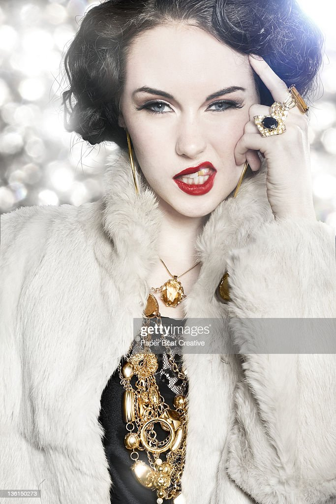 luxurious glamorous woman licking her gold tooth