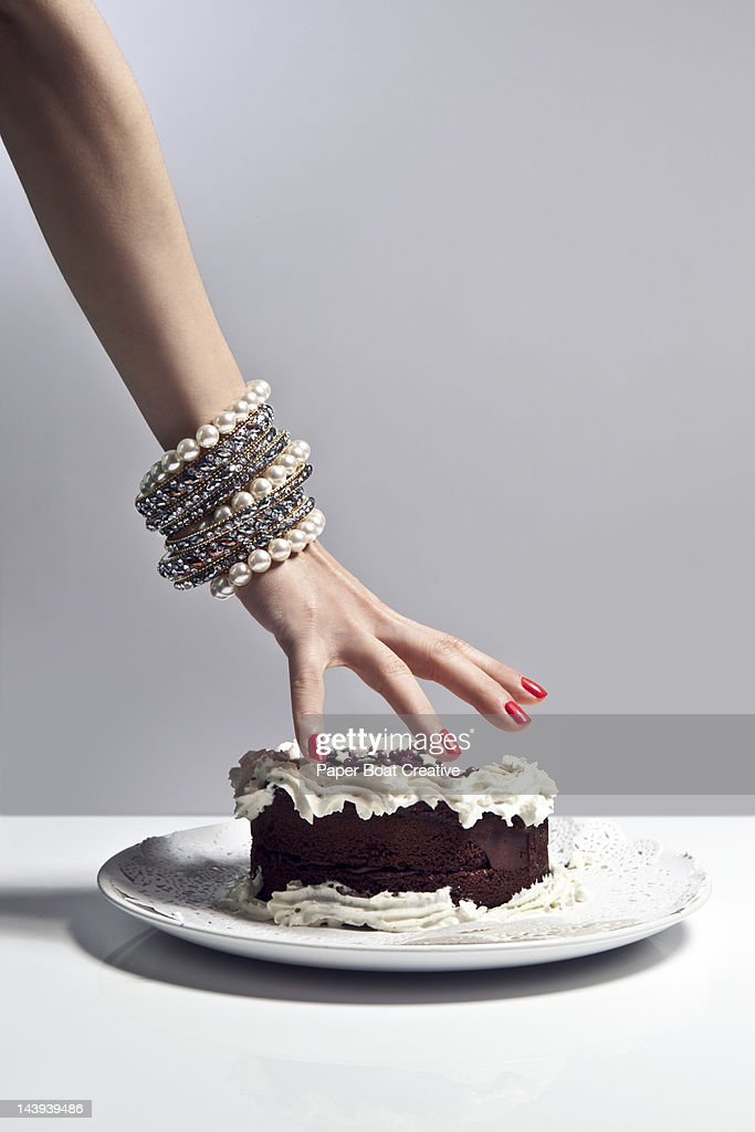 luxurious hand grabbing a large piece of cake : Foto de stock