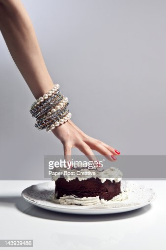 luxurious hand grabbing a large piece of cake : Stock Photo