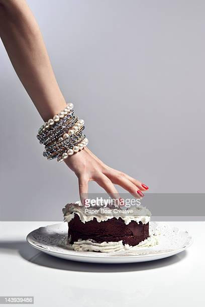 luxurious hand grabbing a large piece of cake
