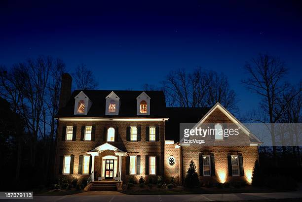 A luxurious large manor home lit up at night