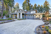 Luxurious new construction home exterior with two garage spaces and wide driveway at sunrise. Northwest, USA