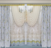 Luxurious window dressing in the interior Curtains with floral pattern made of natural fabric, transparent tulle with ornament and a stylish pelmet.