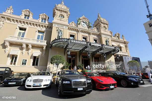 Luxury automobiles including a Bentley second left a RollsRoyce center and a Ferrari sports car second right stand outside the Casino de MonteCarlo...
