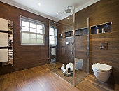 """a guest's bathroom in a luxury new home with walls and floor tiled in wood-effect ceramic tiles. A glass screen enclosed shower area sits near the centre with a """"rainfall"""" shower overhead and hand sho"""