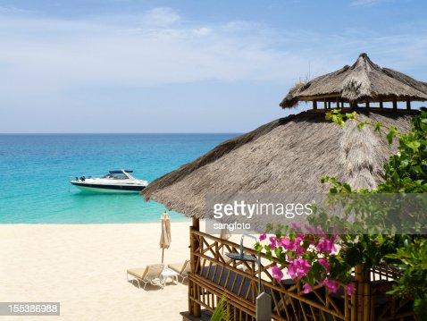 Luxury beach scene with hut and yacht