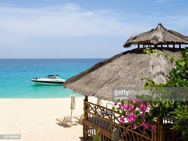 Scène de plage avec hutte et de yacht