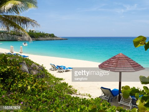 A luxury beach scene with lounge chairs and umbrellas