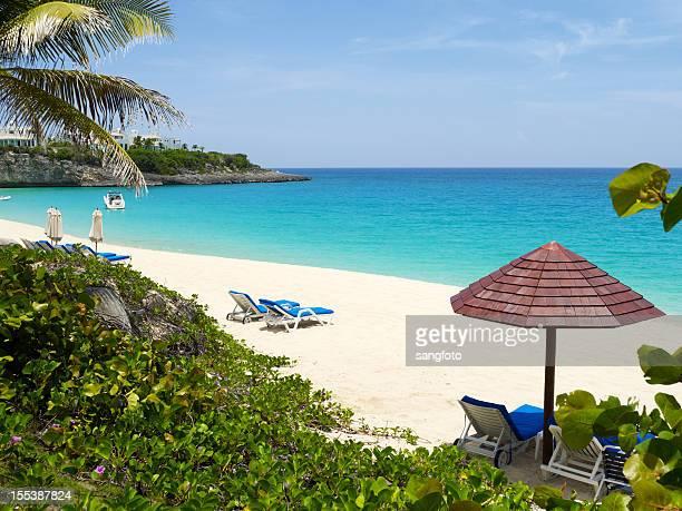Scène de plage avec des chaises longues et parasol
