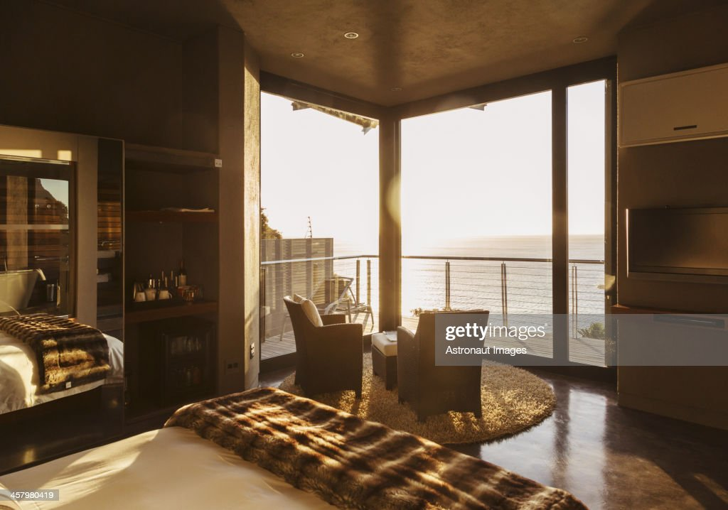 Luxury Bedroom Overlooking Ocean At Sunset Stock Photo