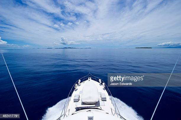 A luxury boat ploughs through a calm turquoise ocean in the Pacific.