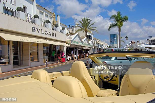 Luxury car and shops at the exclusive yacht harbor of Puerto Banus Marbella Costa del Sol Malaga province Andalusia Spain